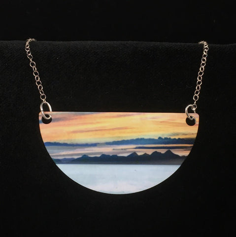 details of the Western Isles necklace - a vibrant sunset in yellows and oranges set against the silhouette of mountains
