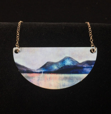 detail image of Sound of Mull necklace - blue mountains sit above a lake shimmering in pinks and blues
