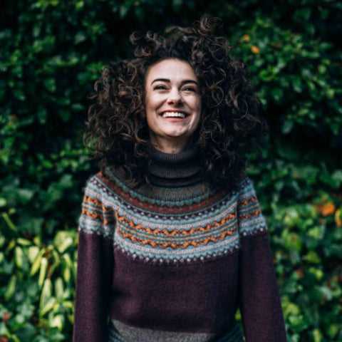 A woman against a background of greenery wearing the Beech Alpine Sweater.