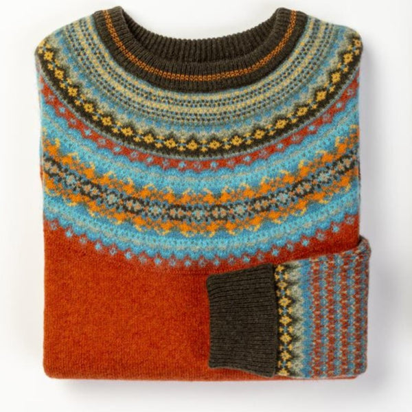 Detail product image of the Pheasant Alpine Sweater. The main body is a burnt orange colour with fairisle knit collar and cuffs in blue, charcoal, orange and yellow.
