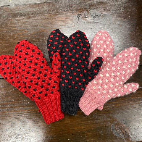 red, black, and pink mittens fanned out on a wooden table