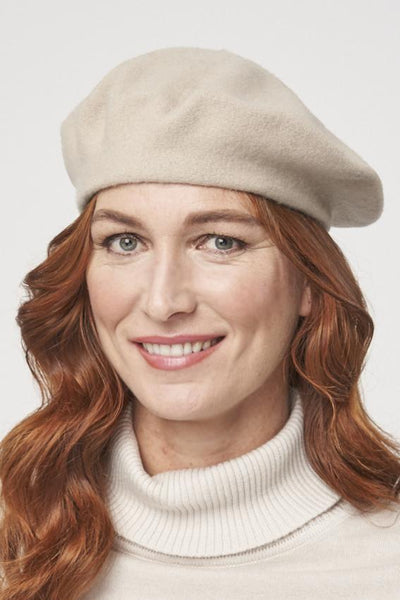 a redhaired model wearing a soft beige beret