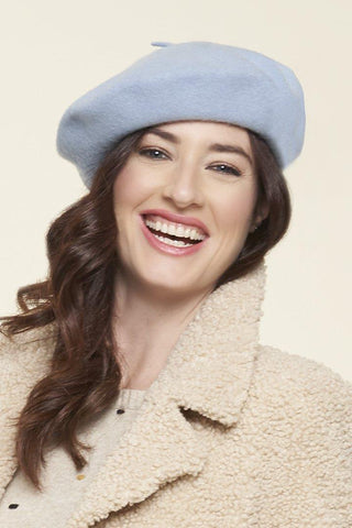 a brunette model laughing, she is wearing an eggshell blue beret