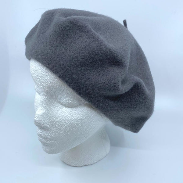 a dark grey tam/beret on a mannequin head