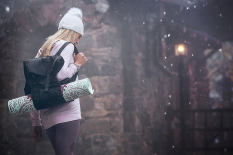 Blonde girl wearing a white beanie and a pink long sleeve walks outside in a wintery atmosphere carrying a black backpack holding a yoga mat