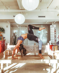 Dark haired woman does a yoga backbend in a sports bra and leggings in a sun lit room on top of a low table