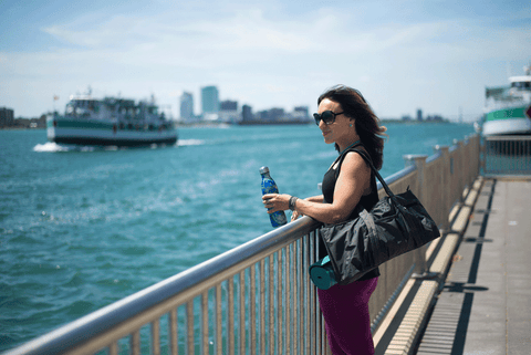 woman standing at Detroit River on a sunny day with dark hair holding a water bottle