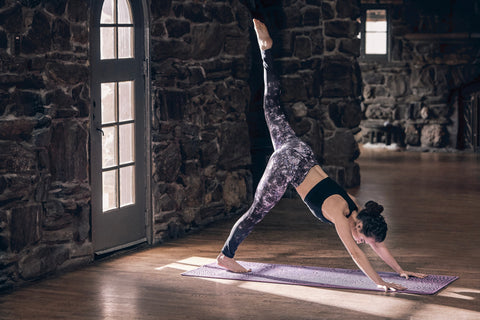 A dark-haired woman wearing a black sports bra and purple patterned yoga pants does 3-legged downward facing dog in a stone lodge