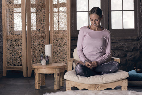 blonde girl in a pink long sleeve and purple patterned pants sits on a low and light colored meditation chair while smiling and looking down