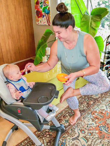 woman feeds child in high chair while doing standing figure 4