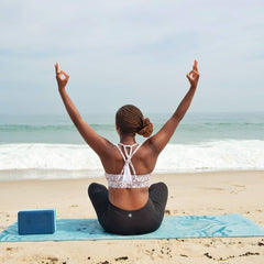 African American woman with her hair in a low bun sits on a yoga mat facing the beach with her arms up in the air and hands in a mudra
