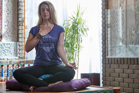 blonde girl in yoga attire sits in meditation cushions while placing her hand on her heart