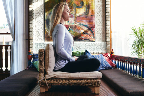 blonde girl wearing a long sleeved shirt sits meditating on a low chair in fancy room