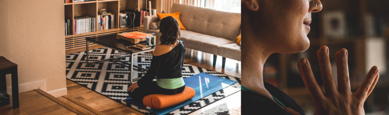 woman sits and meditates in living room