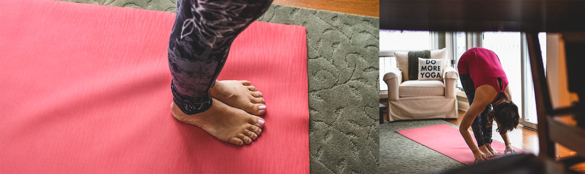 woman does a forward fold on her yoga mat