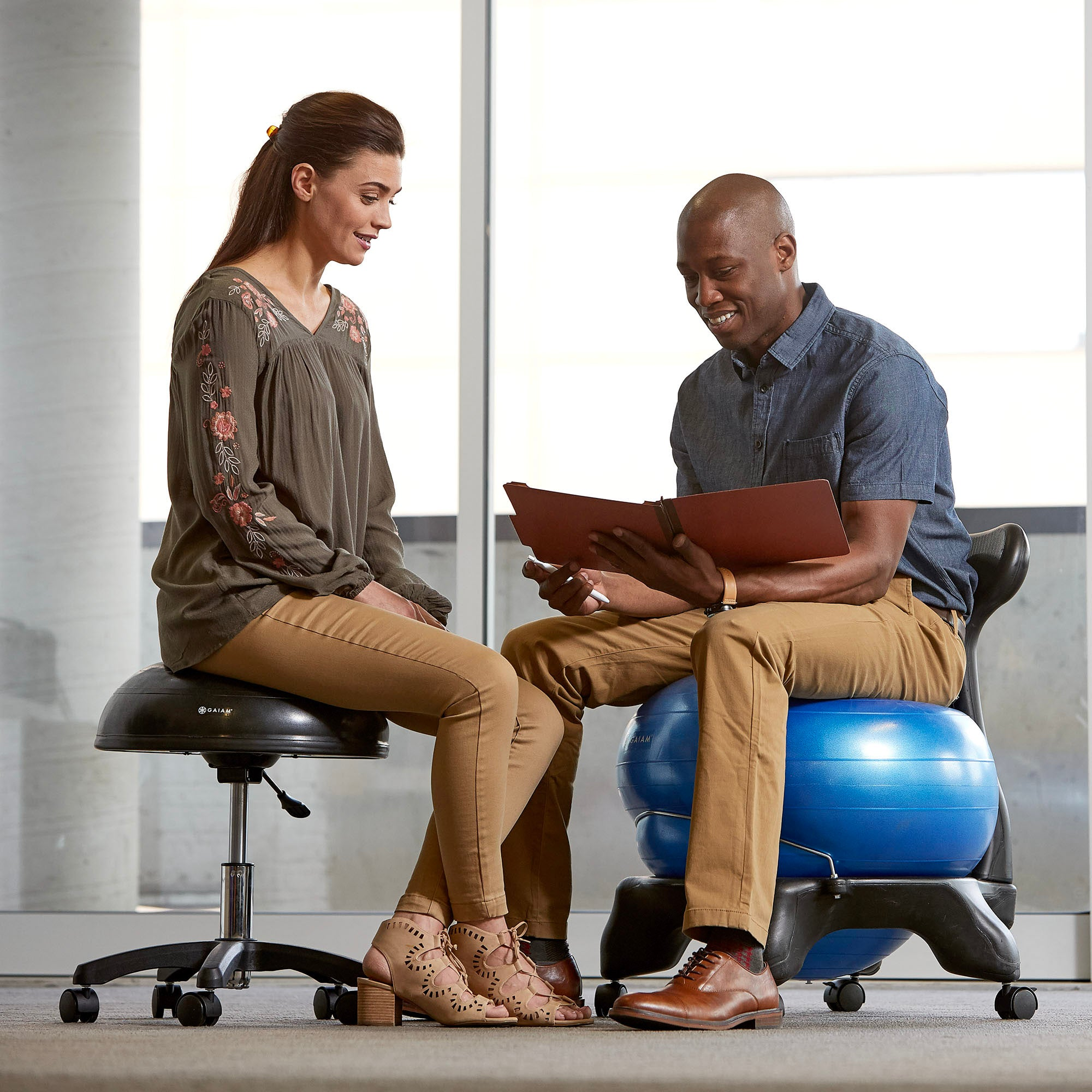 super popular 7be64 46ae7 ... Man sitting on the Blue Classic Balance Ball Chair talking to a woman  ...