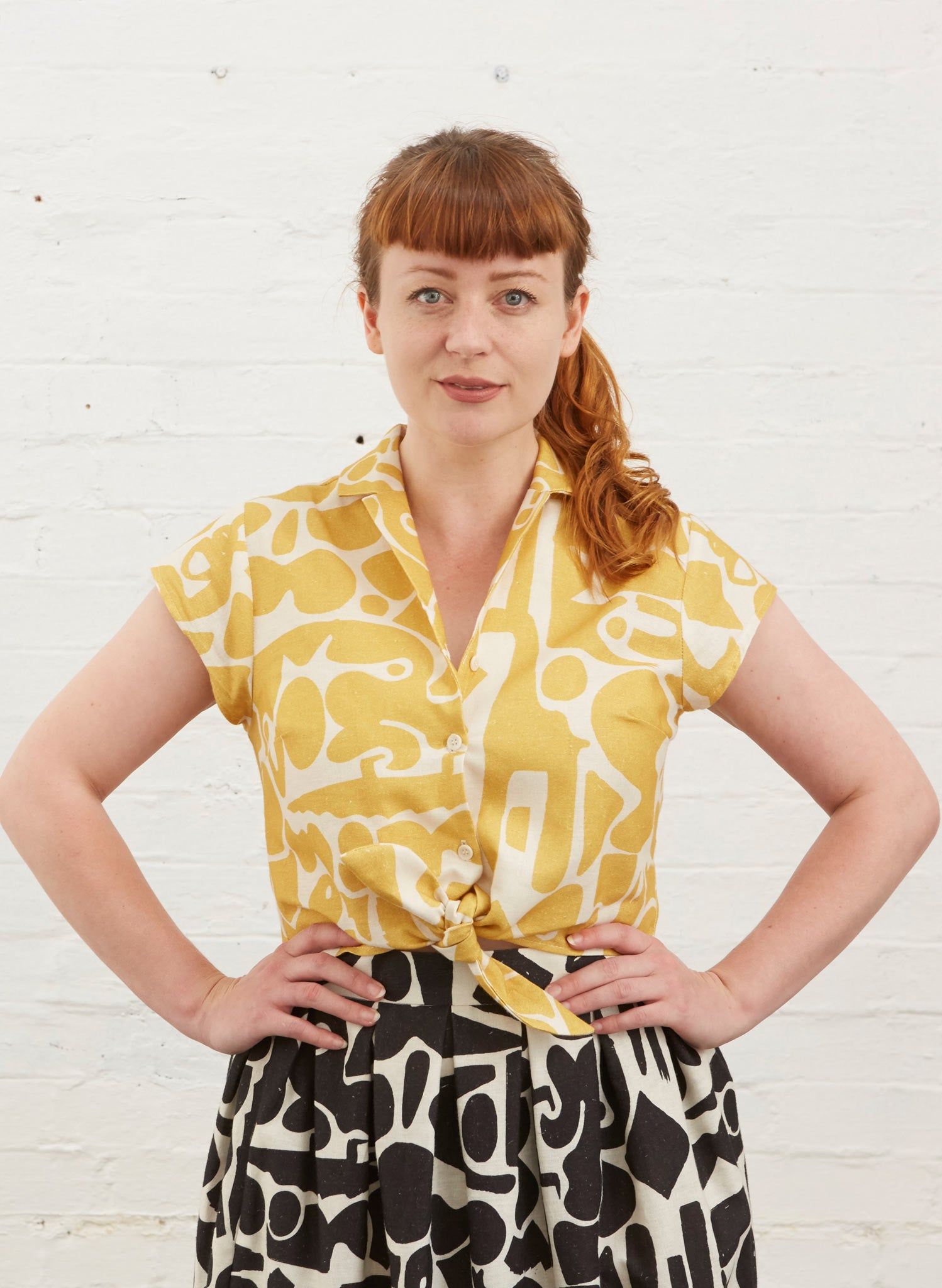 Photo of Alison wearing a cropped tie waist button up blouse with yellow and white abstract shape fabric. Also wearing black and white Ada skirt in same pattern.