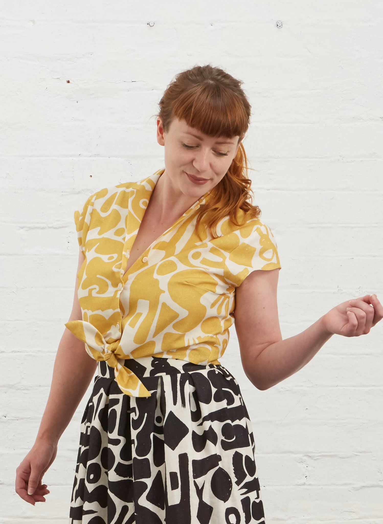 Photo of Alison ( fringed auburn hair )wearing a cropped tie waist button up blouse with yellow and white abstract shape fabric. Also wearing black and white Ada skirt in same pattern.