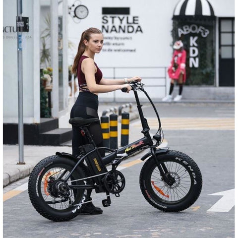 Black AddMotor Motan M150 - Folding Fat Tire Electric Bike - with Female Rider in Street
