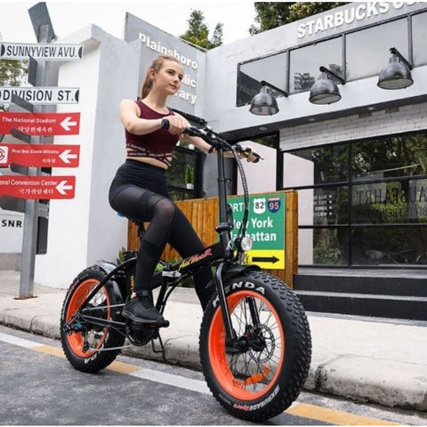 Orange AddMotor Motan M150 - Folding Fat Tire Electric Bike - Female Rider on Street
