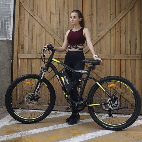 Yellow AddMotor HitHot H1 - Electric Mountain Bike - in front of barn door