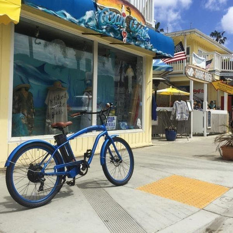 Blue EMOJO Hurricane - Cruiser Electric Bike - In front of a store