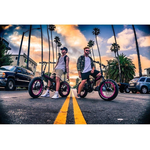 EMOJO Lynx - Fat Tire Folding Electric Bike - Two Riders in the middle of the street