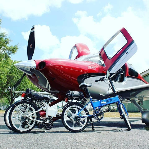 Enzo eBikes - Folding Electric Bike - Multiple in front of airplane