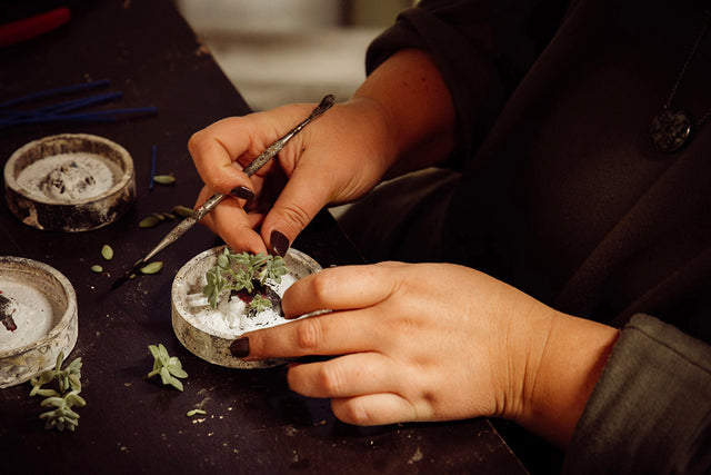 Working hands take live succulents to make one time use molds to make one of a kind jewelry.