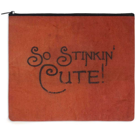 Makeup travel bag has bright orange cotton and rustic style black lettering. Includes a ticking lining with an inside pocket.