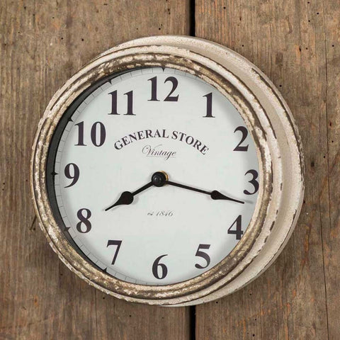 This metal clock has a white distressed finish and reads 'General Store'.