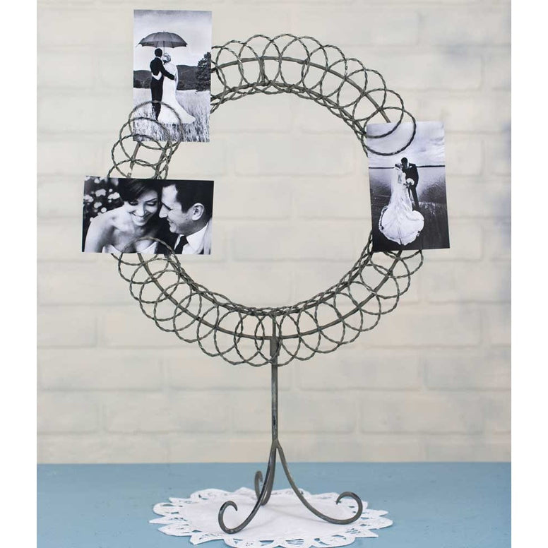 Metal photo caddy has a circular design and wire ring holders for the photos. Hold has a tall three legged stand.