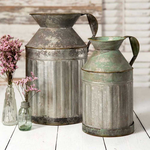 These two milk jugs are made from galvanized metal and have the look of old fashioned milk pitchers.