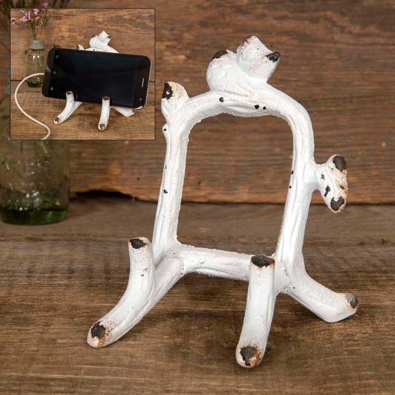 Cell phone holder is made from metal and has a vintage design with white distressed finish and a pair of birds on branches.