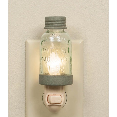 Night light has a hand blown glass and distressed metal mason jar design.