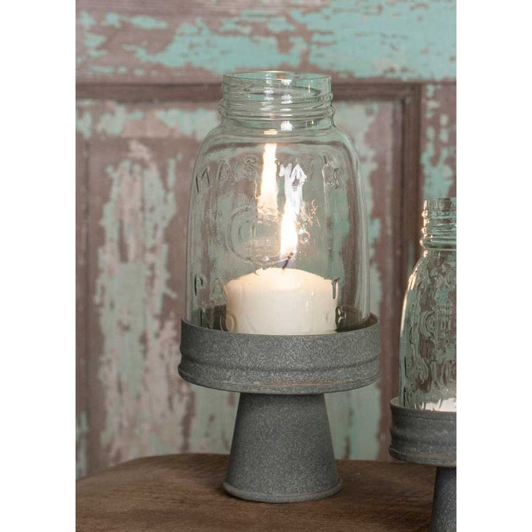 Candle holder has a rustic finished metal base and holds a pint mason jar chimney for safer burning.