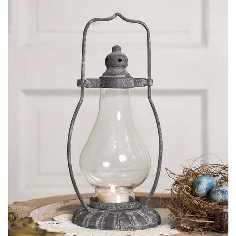 Vintage style lantern has a metal base with a gray rustic finish and includes a glass chimney.