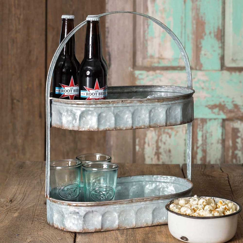 corrugated metal tray that  features two tiers and a handle. The galvanized metal has a distressed look that brings a vintage look into your home decor.