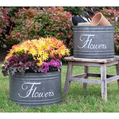 Set of two rustic style bins feature the word 'Flowers' in stylized white script.  Made of distressed finished galvanized metal, these bins come in two sizes and feature handles on either side.