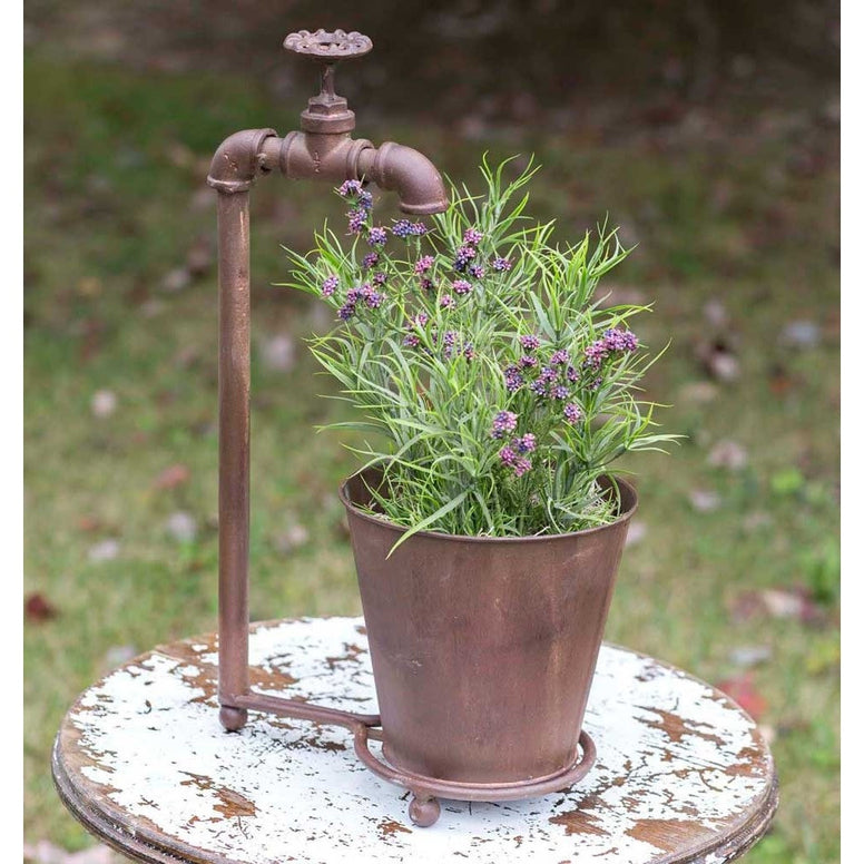 Country style rustic planter features a rusted metal finish and an old fashioned water spigot design. Metal bucket is separate from the water spigot stand.