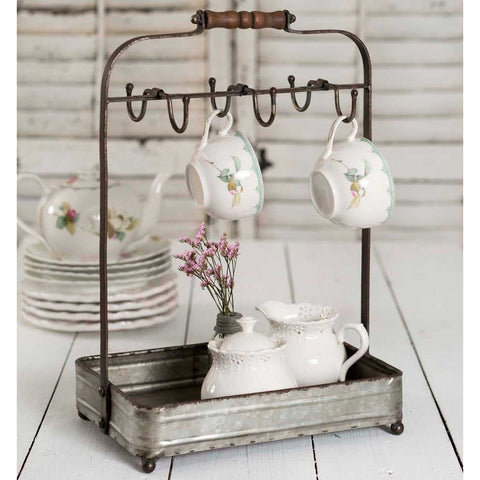 This mug rack features a rustic galvanized metal tray and space for 6 cups or mugs. A convenient metal wire handle topped by a wood holder makes this perfect for carrying.