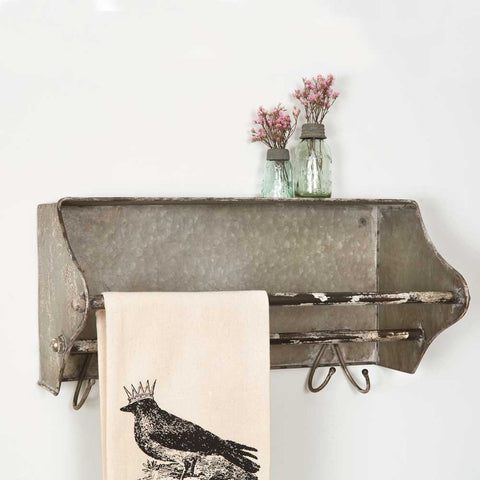 This metal wall rack and towel bar is shaped like a tool box and features a distressed finish.