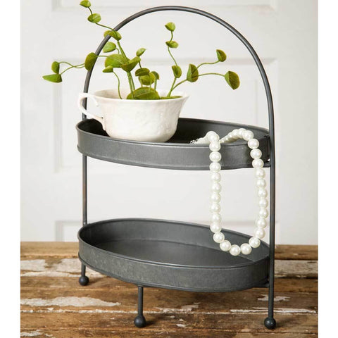 Two-tier farmhouse style tray features a gray galvanized metal finish with oval shaped trays, a curved metal handle and balled feet.
