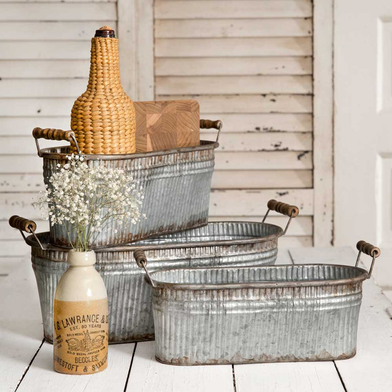 Each corrugated galvanized metal bin is a different size and features a vintage gray distressed finish. These rustic style bins come with wooden handles and nest together for easy shipping and storage.