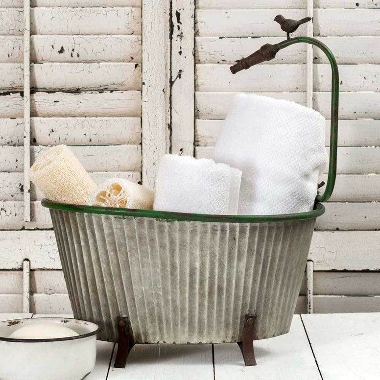 Gray corrugated metal storage bin features a footed bottom and distressed finish. Storage bin also includes a green hose design around the top of the bin.