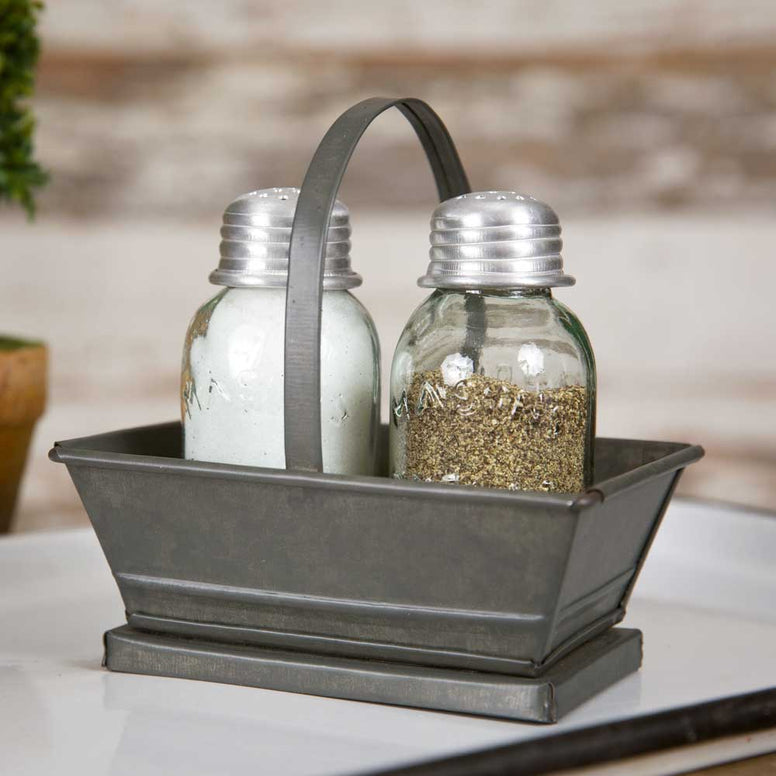 This farmhouse style galvanized metal tote includes two mason jar shakers. Tote has an industrial design and features a handle for easy carrying.