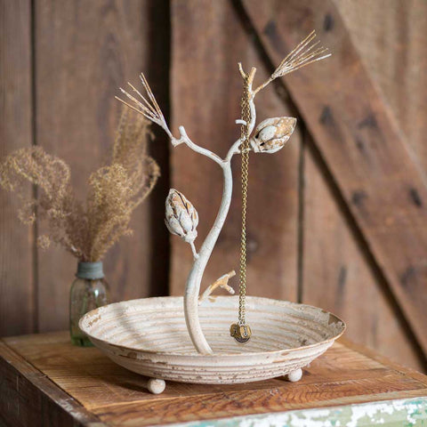 This jewelry tray features a rustic pine bough standing in the center, a circular saucer base and distressed white finish.
