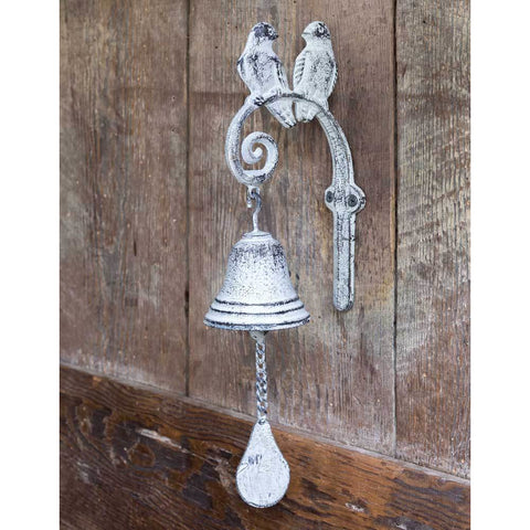 Cast iron dinner bell features two songbirds sitting on the top and a distressed white finish.