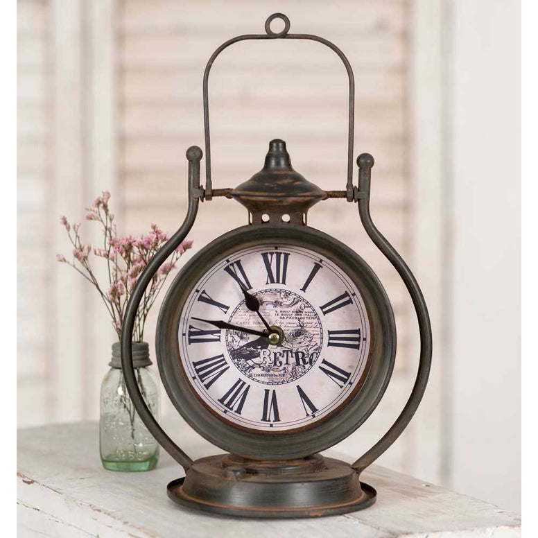 Vintage tabletop clock has a metal base and vintage styled face featuring a Retro design. Comes with a distressed finish.