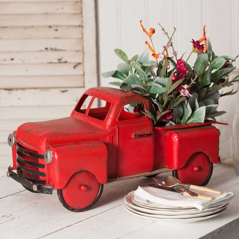 This inspired metal planter features a vintage truck design and distressed red and black finish.